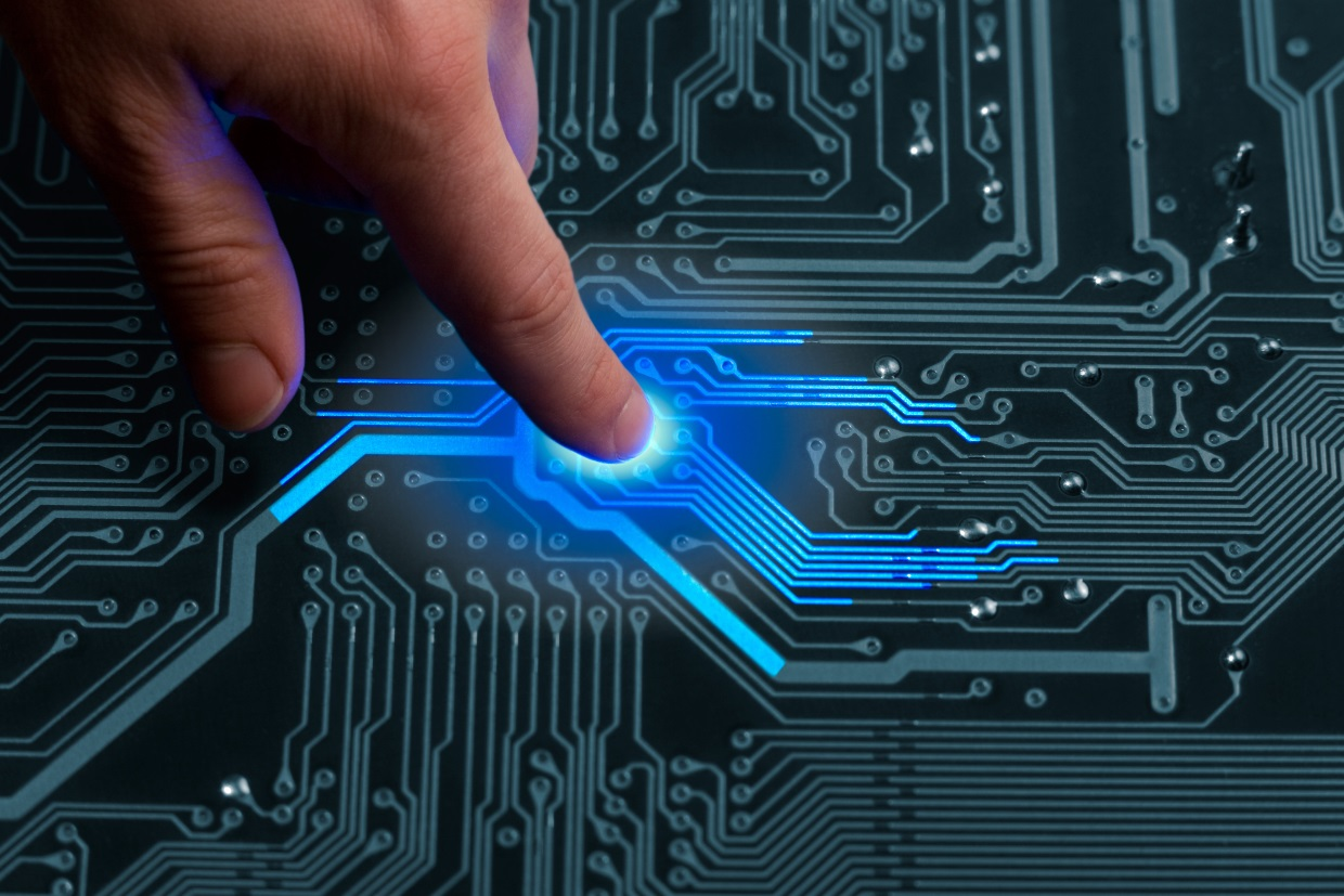 Mans finger is charging passive circuit board with blue energy